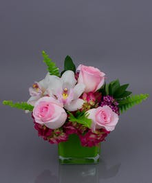 Our Gentle Embrace is a sweet vase designed using fresh roses, orchids, and hydrangea all in a leaf lined cube.  Approximately 8