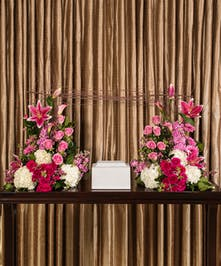 A stunning collection of beautiful flowers artfully designed with birch branches surround the memorial urn.