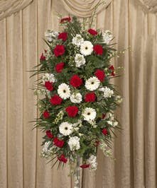 A traditional mix of red and white flowers including gerbera daisies, stock and carnations make an impressive display at the funeral home.