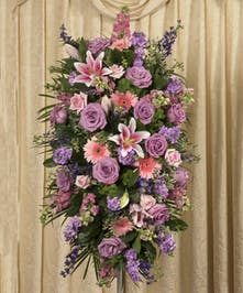 Pastel-colored roses, gerbera daisies, lilies and more designed in a traditional standing spray make the Soft Colored Standing Spray a wonderful choice for your loved one.