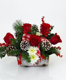 This rustic arrangement is designed in our realistic ceramic birch log planter and includes a variety of fresh cut winter greens, carnations or roses, and berries.