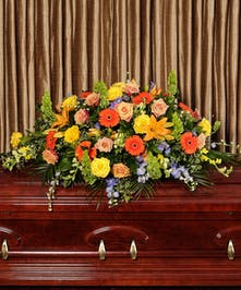 A beautiful collection of bold and colorful flowers adorn the casket to celebrate the fond memories of a loved one.