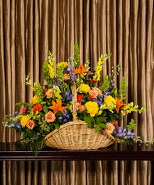 A bold and colorful collection of flowers designed in a basket to celebrate the fond memories of a loved one.
