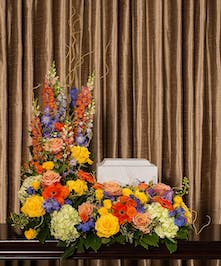 A stunning collection of beautiful flowers artfully designed to surround the memorial urn.