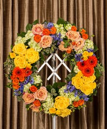 A bold collection of colorful flowers designed pave style in the form of a wreath.