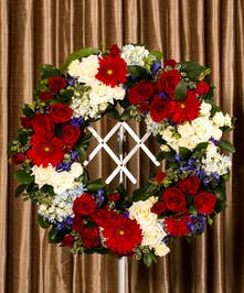 A patriotic tribute designed pave style in the form of a wreath.