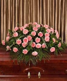 A beautiful collection of pink carnations artfully designed to adorn the casket