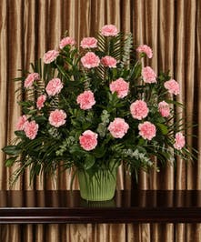 A beautiful collection of pink carnations artfully designed into an impressive display for the service.