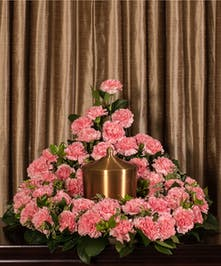 A beautiful collection of pink carnations artfully designed to embrace the memorial urn.