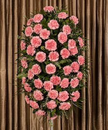 A beautiful collection of pink carnations artfully designed into an impressive display for an easel.
