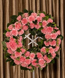 A beautiful collection of pink carnations artfully designed into a beautiful display for the service.
