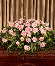 A beautiful collection of pink roses artfully designed to adorn the casket