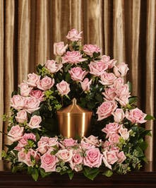A beautiful collection of pink roses artfully designed to embrace the memorial urn.