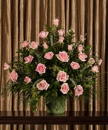 A beautiful collection of pink roses artfully designed into an impressive display for the service.
