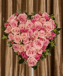 A beautiful collection of pink roses artfully designed into a beautiful display for the service.