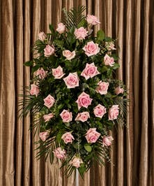 A beautiful collection of pink roses artfully designed into an impressive display for an easel.