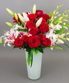 Roses, hydrangea, and orchids designed in a contemporary white vase.