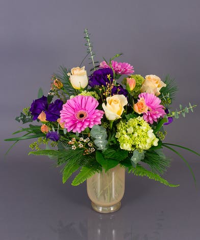 We design roses, hydrangea, lissianthus, and gerbera daisies inner imported pastel hurricane vases to create out wonderful Winter Delight vase.