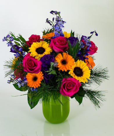 Part of our Emilia vase collection, the Winter's Glow arrangement is a very full design of roses, sunflowers, gerbera daisies, delphinium, lisianthus, and winter greens.
