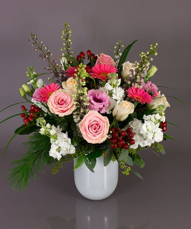 Part of our Emilia vase collection, the Winter's Grace arrangement is a very full design of roses, gerbera daisies, stock, delphinium, lisianthus, berries and winter greens.