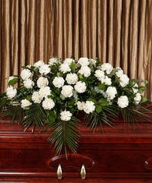 A beautiful collection of white carnations artfully designed to adorn the casket