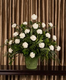 A beautiful collection of white carnations artfully designed into an impressive display for the service.