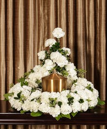 A beautiful collection of white carnations artfully designed to embrace the memorial urn.