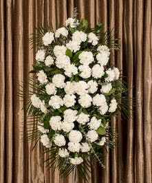 A beautiful collection of white carnations artfully designed into an impressive display for an easel.