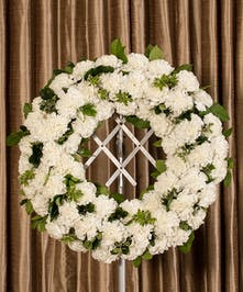 A beautiful collection of White carnations artfully designed into a beautiful display for the service.