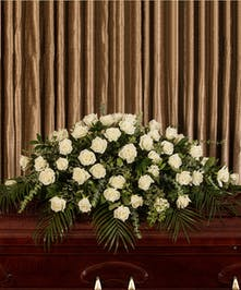 A beautiful collection of white roses artfully designed to adorn the casket