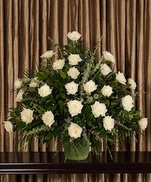 A beautiful collection of white roses artfully designed into an impressive display for the service.