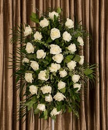 A beautiful collection of white roses artfully designed into an impressive display for an easel.