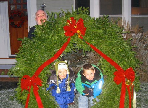 Paul Sr. celebrates Christmas with his grandchildren near an enormous wreath